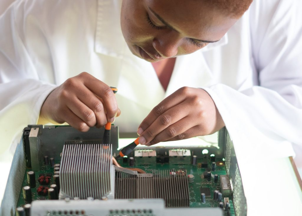 crop-focused-repairman-fixing-graphics-card-on-computer-3825582